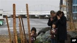 Một gia đình cầu nguyện trước một bàn thờ được đặt tạm nơi khu xóm đã bị tàn phá vì sóng thần cách đây một năm
