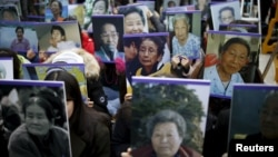 """Students hold portraits of deceased former South Korean """"comfort women"""" during a weekly anti-Japan rally in front of the Japanese Embassy in Seoul, South Korea, Dec. 30, 2015."""