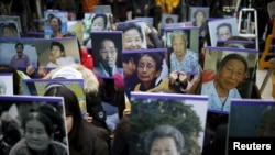 """Sinh viên cầm di ảnh của các """"an uỷ phụ"""" Hàn Quốc trong một cuộc biểu tình chống Nhật trước Đại sứ quán Nhật tại Seoul, Hàn Quốc, 30/12/2015."""