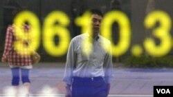 Seseorang mengamati indeks saham Nikkei 225 di Tokyo, Jepang. Indeks Nikkei turun lebih dari dua persen hari Senin (8/8).