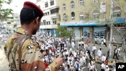 Army soldier watches as anti-government protesters march during a demonstration demanding the ouster of Yemen's President Ali Abdullah Saleh in the southern city of Taiz, April 26, 2011