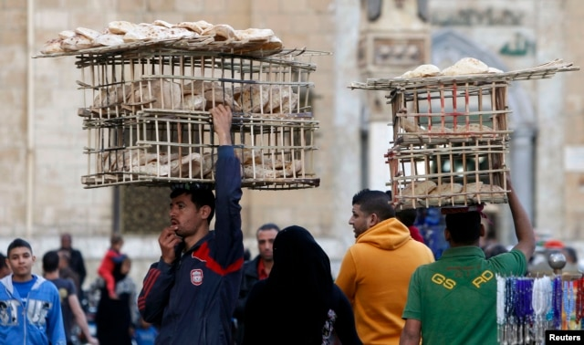 Egyptian men sell bread as they balance the trays on their heads near Al Hussein mosque in Old Cairo, Mar. 17, 2013.