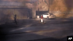 Masked Bahraini anti-government protesters run through smoke after setting tires alight on a road in the village of Dumistan, January 7, 2013.