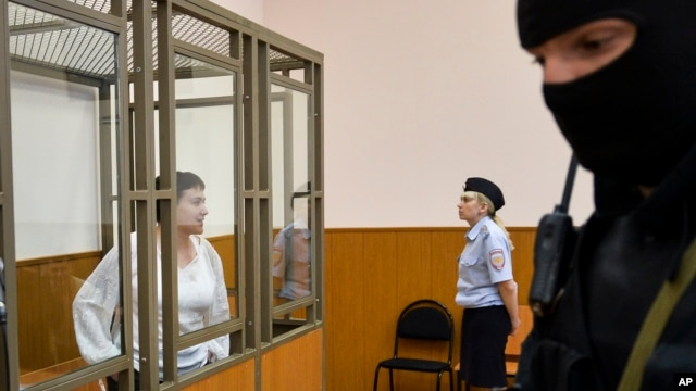FILE - Jailed Ukrainian pilot Nadiya Savchenko (L) stands in a defendant's cage during a court hearing in the town of Donetsk, Rostov-on-Don region, Russia, Sept. 29, 2015.
