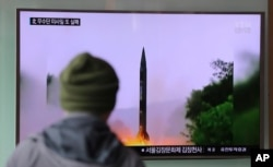 FILE - A man in South Korea watches a TV news program showing a missile launch conducted by North Korea.