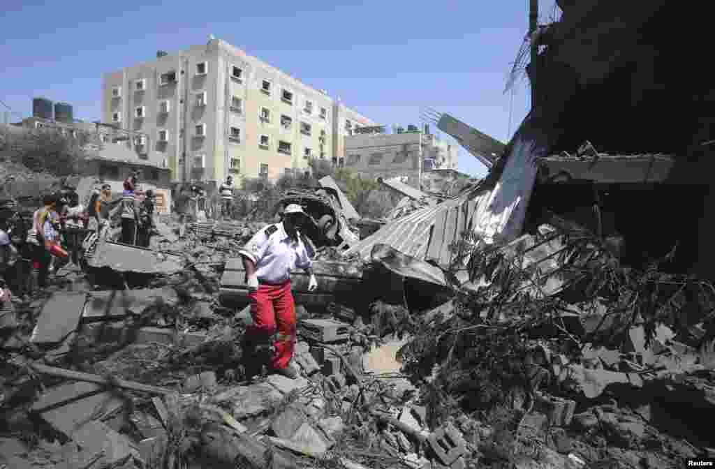 A Palestinian medic walks amidst the debris of a house which police said was destroyed in an Israeli air strike in Rafah in the southern Gaza Strip July 14, 2014.