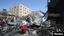 7月14日,一个巴勒斯坦医护人员在加沙地带南部的一栋被以色列飞机炸毁的房子废墟上寻找救助的目标。