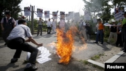 A man from an anti-North Korea and conservative civic group burns an effigy of North Korean leader Kim Jong Un during an anti-North Korean rally near the demilitarized zone separating the two Koreas in Paju, South Korea, August 11, 2015.