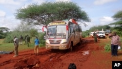Kenyan security forces and others gather around the scene on an attack on a bus about 50 kilometers outside the town of Mandera, near the Somali border in northeastern Kenya, Nov. 22, 2014.