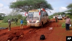Kenyan security forces and others gather around the scene on an attack on a bus about 50 kilometers (31 miles) outside the town of Mandera, near the Somali border in northeastern Kenya, Nov. 22, 2014.