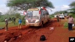 FILE - Kenyan security forces and others gather near the scene of a deadly bus attack 50 kilometers (31 miles) outside the town of Mandera, near the Somali border in northeastern Kenya, Nov. 22, 2014.