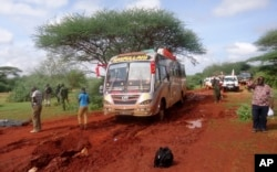 FILE - Kenyan security forces and others gather around the scene on an attack on a bus about 50 kilometers (31 miles) outside the town of Mandera, near the Somali border in northeastern Kenya, Nov. 22, 2014.