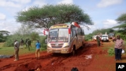 Kenyan security forces and others gather at the scene of a bus attack near the town of Mandera, close to the Somali border, Nov. 22, 2014.