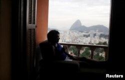 A guest relaxes with the The Sugar Loaf mountain in the background at Pousada Favelinha (Little favela) hostel in Pereira da Silva favela, in Rio de Janeiro, Brazil, April 29, 2016.