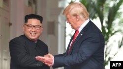 도널드 트럼프 미국 대통령이 12일 싱가포르 카펠라 호텔에서 열린 미북 정상회담에 앞서 김정은 북한 국무위원장과 악수하며 왼손으로 단독회담장 방향을 가리키고 있다.
