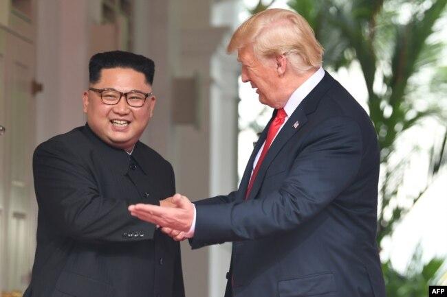 도널드 트럼프 미국 대통령이 김정은 북한 국무위원장과 악수하며 왼손으로 단독회담장 방향을 가리키고 있다.