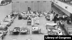 """FILE - In this 1918 file photo made available by the Library of Congress, volunteer nurses from the Red Cross tend to influenza patients in the Oakland Municipal Auditorium, used as a temporary hospital. (Edward A. """"Doc"""" Rogers/Library of Congress)"""