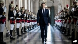 French President Emmanuel Macron walks through the Galerie des Bustes (Busts Gallery) to access the Versailles Palace's hemicycle where both houses of parliament (National Assembly and Senate) are gathered in the palace of Versailles, outside Paris, July