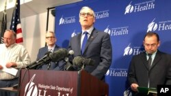 Washington Gov. Jay Inslee, center, speaks Tuesday Jan. 21, 2020, at a news conference in Shoreline, Wash., following the announcement that a man in Washington state is the first known person in the United States to catch a new type of coronavirus. (AP Photo/Carla K. Johnson)