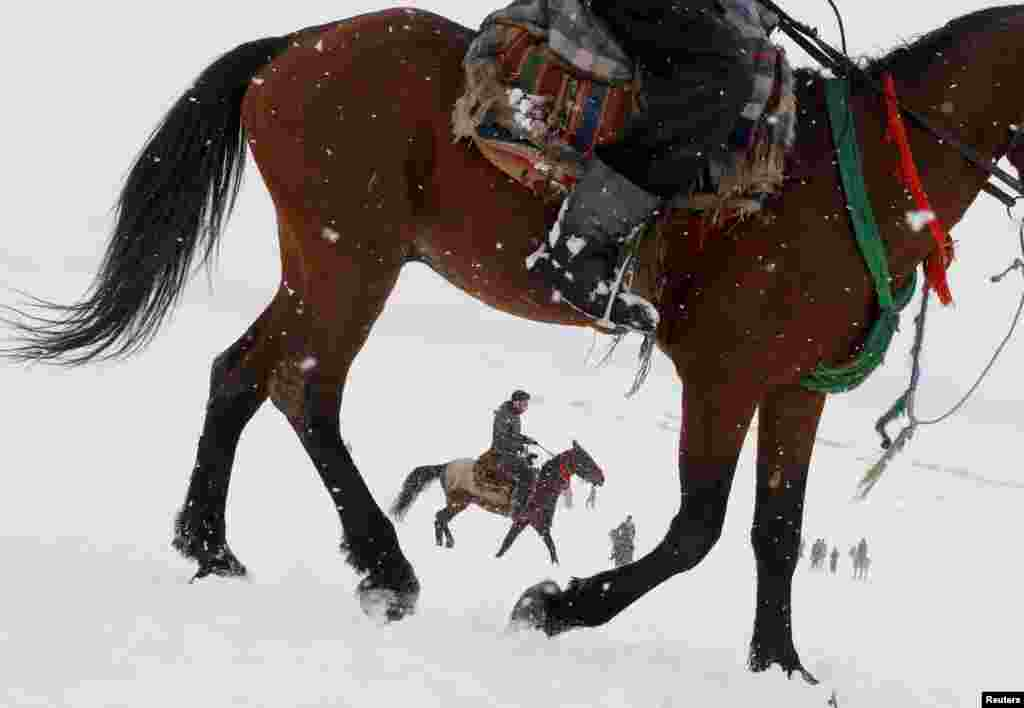 Afghan men ride horses on the snow-covered ground on the outskirts of Kabul.
