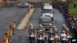 Defense force personnel and hospital staff salute a procession for former South African president Nelson Mandela as it leaves the military hospital in Pretoria, Dec. 11, 2013.