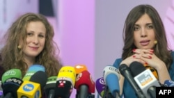 Two members of Russian punk group Pussy Riot, Nadezhda Tolokonnikova (R) and Maria Alyokhina (L), answer journalists' questions during their news conference in Moscow on December 27, 2013.