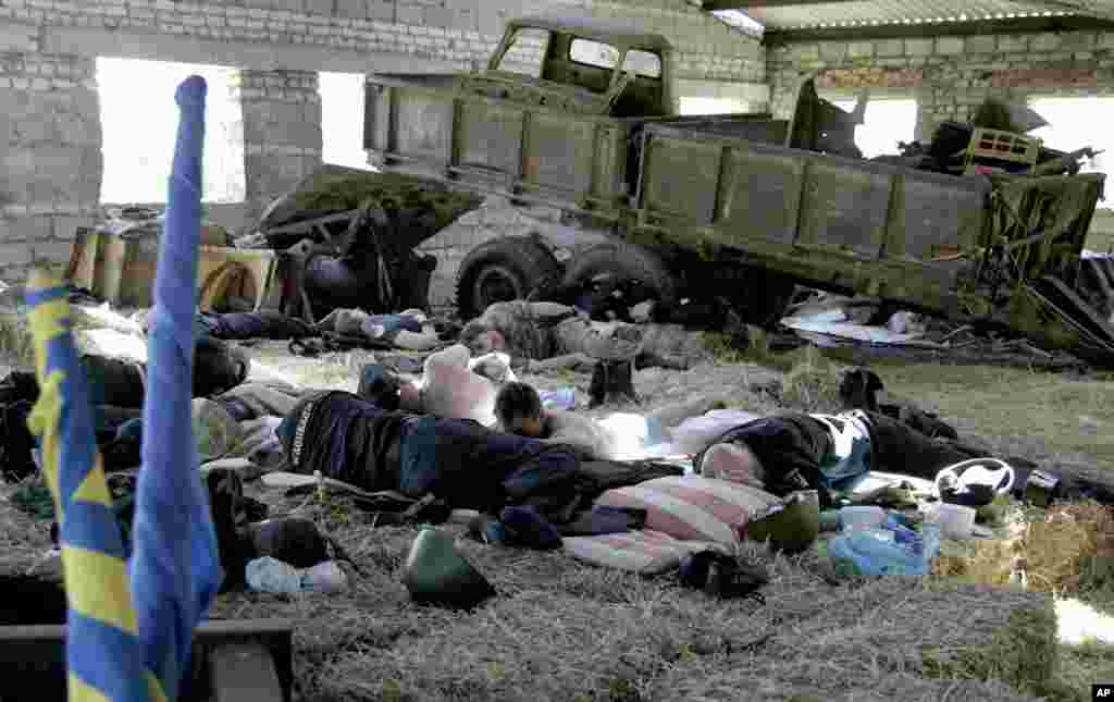 Troops with the Donbass Battalion, a volunteer militia group that has stated its intent to fight in support of Ukrainian unity, sleep in the hay, in the village of Velyka Novosilka, near Donetsk, eastern Ukraine, May 16, 2014.