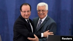 Palestinian President Mahmoud Abbas (R) and his French counterpart Francois Hollande embrace during a joint news conference in the West Bank city of Ramallah, Nov. 18, 2013.