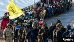 Members of various anti-government paramilitary groups march along a street during a show of force in Kyiv, Jan. 29, 2014.