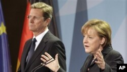 German Chancellor Angela Merkel, right, and Vice Chancellor Guido Westerwelle, left, address the media during a joint news conference Berlin, Germany, March 12, 2011