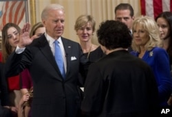 FILE - Vice President Joe Biden takes the oath of office during the 57th Presidential Inauguration official swearing-in ceremony at the Naval Observatory in Washington, Jan. 20, 2013.