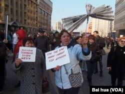 4月13日的莫斯科媒体自由集会上,两名妇女手举标语抗议媒体谎言宣传。左边标语:关掉电视,启动大脑思考。右侧标语:如果对你撒谎,那意味着他们认为你是傻瓜。 (美国之音白桦拍摄)