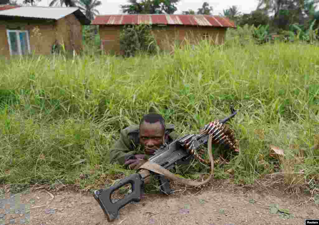 A soldier for the Armed Forces of the Democratic Republic of the Congo (FARDC) rests next to a road after the Islamist rebel group called the Allied Democratic Forces (ADF) attacked the area around Mukoko village, North Kivu province, Dec. 11, 2018.