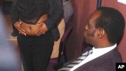 L'archevêque Gilbert Deya, à droite, regarde une femme enceinte Deonna Dakkins-Scott, montrant son ventre à des journalistes lors d'une conférence de presse à Glasgow, Écosse, 29 septembre 2004.