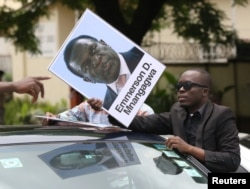 A protester holds a poster showing support for ousted Zimbabwean Vice President Emmerson Mnangagwa, in Harare, Zimbabwe, Nov. 18, 2017. Mnangagwa is to be sworn in as president Wednesday or Thursday.