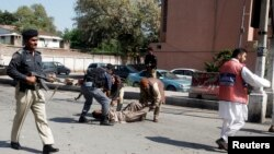 Security officials carry away an injured man from the site of a bomb blast in Peshawar, March 29, 2013.