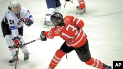 Canada's Caroline Quellette and US Kacey Bellamy vie for puck during gold medal match at the IIHF Women's World Ice Hockey Championships in Finland, 12 Apr 2009