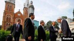 Menlu AS John Kerry (kanan) disambut para pastor Vietnam saat hendak mengikuti misa di Katedral Notre Dame di kota Ho Chi Minh (14/12).
