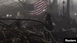 Seorang warga New York berjalan di antara puing-puing rumah yang hancur oleh Badai Sandy. (Foto: Dok)