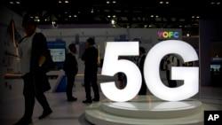 Visitantes se paran cerca de un logotipo 5G en una pantalla del fabricante chino de cables de fibra óptica YOFC en la PT Expo en Beijing.