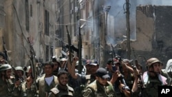 In this photo taken during a government-organized tour, Syrian soldiers celebrate after they regained control of the district of Midan, in the southern part of Damascus, Syria, Friday, July 20, 2012. Syrian troops and tanks on Friday drove rebels from a D
