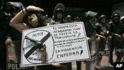 Una mujer porta un cartel contra el aumento de la violencia en el país durante una manifestación en Caracas.