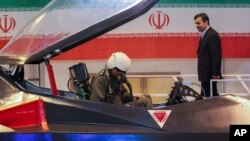 Iranian President Mahmoud Ahmadinejad, center, listens to an unidentified pilot during a ceremony to unveil Iran's newest fighter jet, Qaher-313, or Dominant-313,which officials claim can evade radar, in Tehran, February 2, 2013.