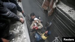 Syria Civil Defense members help an unconscious woman from a shelter in the besieged town of Douma, Eastern Ghouta, Damascus, Syria, Feb. 22, 2018.