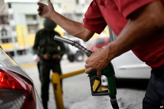 Un trabajador sostiene una bomba de gasolina en una estación de servicio de la compañía petrolera estatal PDVSA en Caracas, Venezuela, el lunes 25 de mayo/2020.