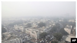 This combination of Nov. 1, 2019, top, and April 20, 2020 photos shows New Delhi's skyline. India's air quality improved drastically during a nationwide lockdown to curb the COVID-19 coronavirus.