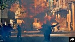 Polisi anti huru hara menembakkan gas air mata saat memblokir Rasheed Street saat bentrokan dengan demonstran anti-pemerintah di Baghdad, Irak, 22 November 2019. (Foto: AP)