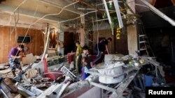 Warga setempat memotret reruntuhan pasca serangan bom di sebuah kedai di Baghdad (17/6). Sedikitnya tujuh warga sipil tewas dan 25 orang cedera dalam ledakan bom di sebuah restoran di kota Taji, Irak utara,.