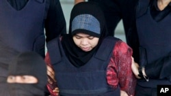 Indonesian Siti Aisyah is escorted by police as she leaves after a court hearing at Shah Alam High Court in Shah Alam, Malaysia, March 22, 2018. Aisyah and Doan of Vietnam have pleaded not guilty of killing Kim Jong Nam on Feb. 13, 2017 at a crowded Kuala Lumpur airport terminal.