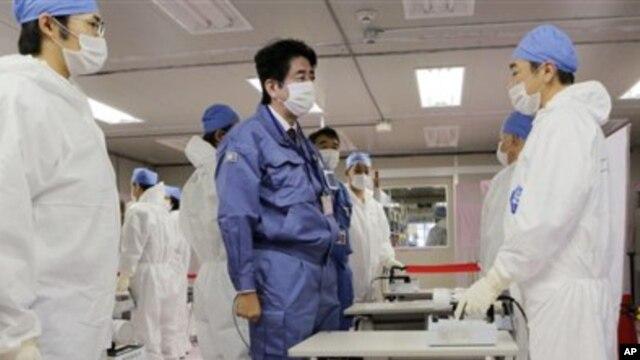 Perdana Menteri baru Jepang, Shinzo Abe (tengah), berbincang dengan pekerja di Pusat Operasi Darurat Tokyo Electric Power Co.(TEPCO) di PLTN Okuma, Fukushima, Jepang (29/12).